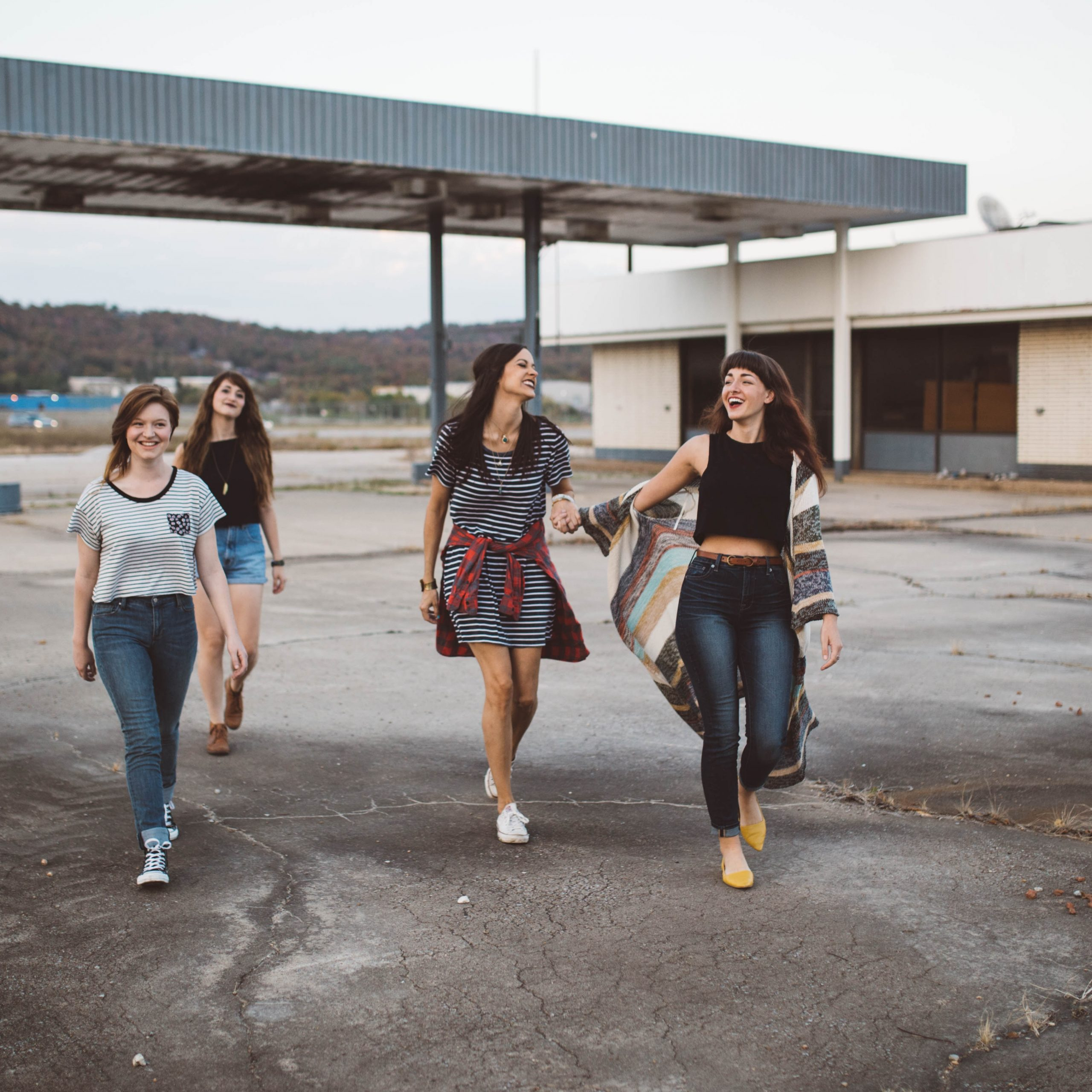 four girls walking near warehouse during daytime