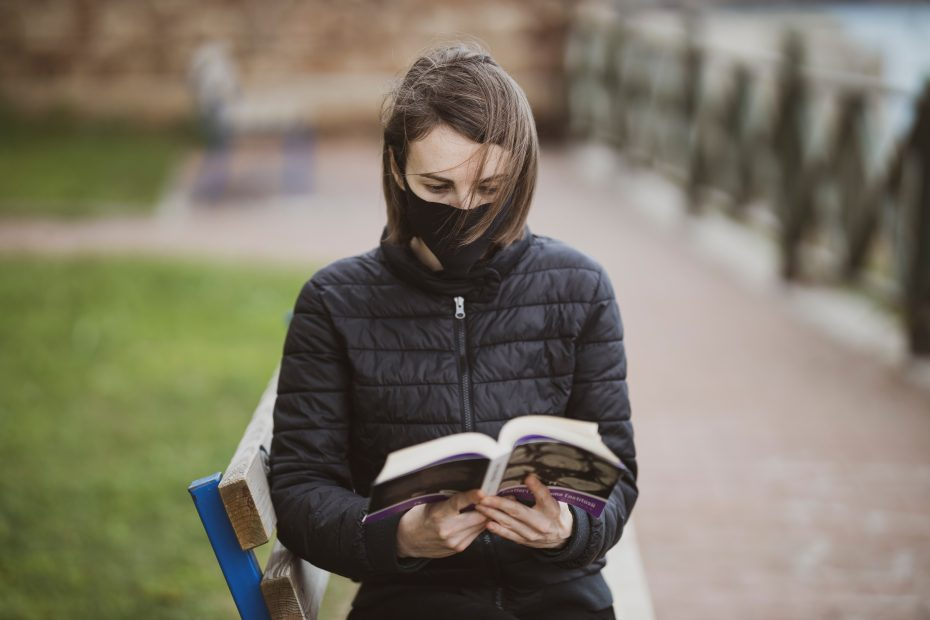woman in black jacket sitting on bench while reading book during daytime