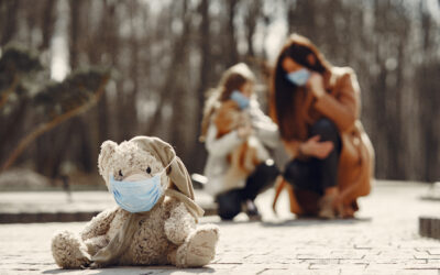 Shabby teddy bear in medical mask sitting on pavement against blurred mom and kid in park